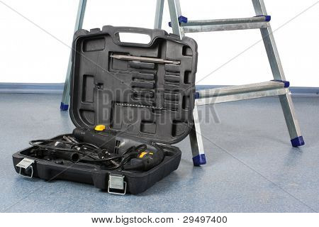 open tool box stands near the step-ladder