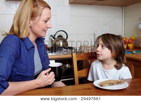 Mother and her son sits at kitchen table and have a conversation