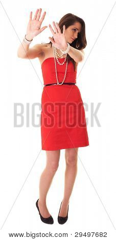 Young attractive brunette in red dress makes stay away, stop gesture, studio shoot isolated on white