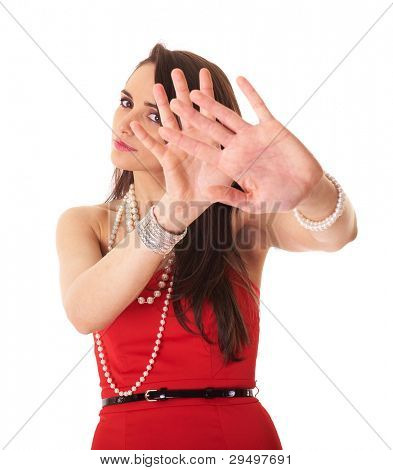 Young attractive brunette in red dress makes stay away, stop gesture using her both hands, studio shoot isolated on white