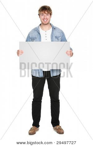 Man showing sign standing in full body. Casual young guy holding blank empty banner sign isolated on white background. Caucasian male model in his twenties.