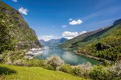 Flam Village With Ship In Harbor Against Fjord During Spring Time, Norway poster
