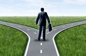 picture of symmetrical  - Career decision for a business man at a cross roads standing at a horizon with grass and blue sky showing a fork in the road representing the concept of a strategic dilemma choosing the right direction to go when facing two equal or similar job options - JPG