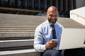 African businessman working on laptop outside a building. Happy black man sitting on stairs working  poster