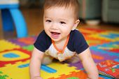 stock photo of crawling  - A cute young boy baby playing inside home with colorful toys - JPG