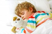Adorable Little Blond Kid Boy In Colorful Nightwear Clothes Sleeping And Dreaming In His White Bed W poster