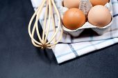 Eggs in cardboard box, towel and whisker closeup on backboard background. Eggs, whisker, towel and o poster