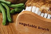 Wooden vegetable brush (with words engraved) on cutting board with wet potatoes and green beans.   M