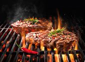 Beef steaks sizzling on the grill with flames poster