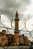 Historical Minaret Behind Fence In Nicosia, Capital City Of Cyprus. Religious Tower With Clouds. Col poster