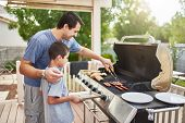 father teaching son how to grill hot dogs and bonding poster