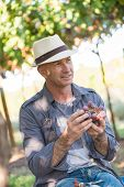 Winegrower Man In Straw Hat Holding Bunch Of Red Grapes. Traditional And Natural Winery Farm. Adult  poster