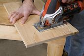 Carpenter sawing wooden board