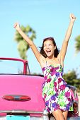 Summer vacation car road trip freedom concept. Happy woman cheering joyful during holiday travel in