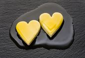 Two Heart-shaped Pieces Of Butter Melting On Black Pan poster