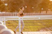 Beautiful Sporty Young Woman Running Over Bridge Early In Morning, Sunflare Effect, Empty Space poster