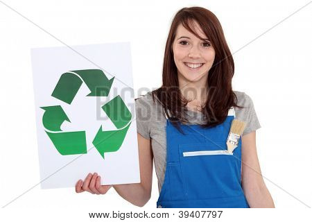 A female manual worker holding a recycle sign.