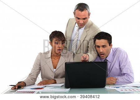 Gerente y sus empleados sorprendidos mirando un ordenador portátil