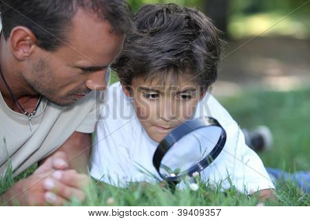father and kid with magnifying glass
