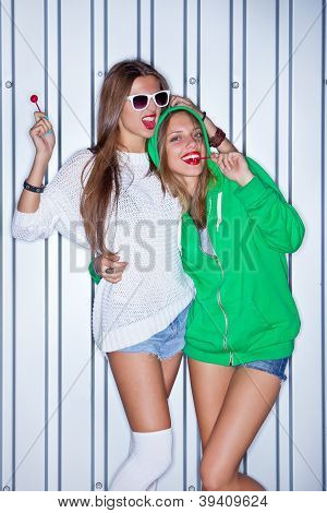 two beautiful young girls with red lollipops near the wall