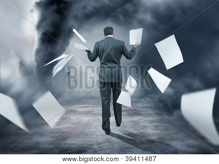 A Businessman Letting go of paperwork in a storm