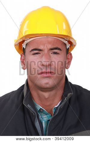 A construction worker with a weird expression.