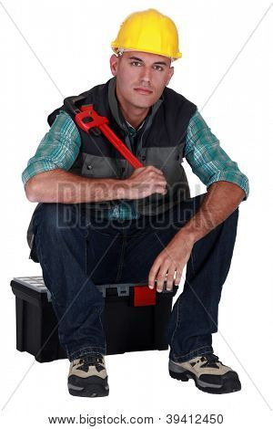 craftsman sitting on toolbox holding adjustable spanner