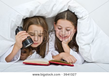 Two Girls Reading Under Blanket