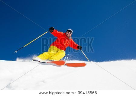 Skiing, Freeride in fresh powder snow - man skiing downhill