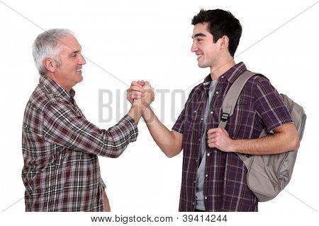 Mature man and young man handshaking