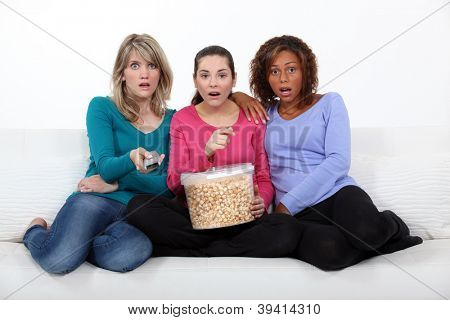 Three scared women sat on sofa watching movie