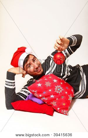Smiling Young Man Wearing Santa Claus Hat With The Pillows And The Ball Isolated On White Background