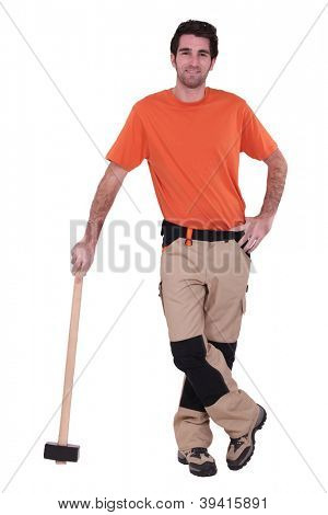 Handyman wearing patched trousers and leaning against a mallet