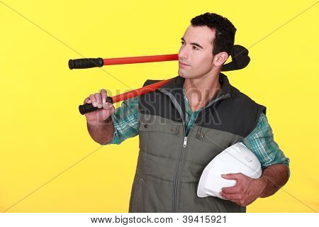 Confident manual worker holding hard hat and bolt cutter