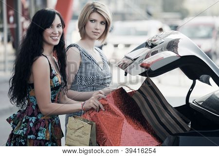 Two young woman with shopping bags on a car parking