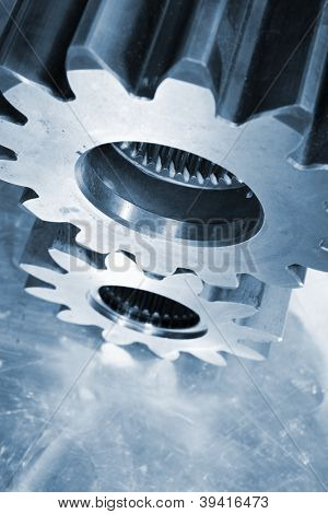 gears and cogs in steel set against brushed titanium, focus on top gear, blue toning concept