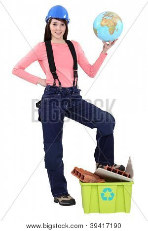 portrait of cute female bricklayer holding globe with foot resting on recycling tub