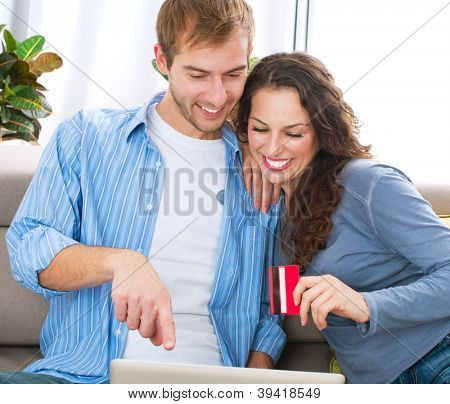 Online Christmas Shopping.Happy Smiling Couple Using Credit Card to Internet Shop on-line. Young couple with Laptop Computer and Credit Card buying online. Christmas and New Year Gifts. e-shopping