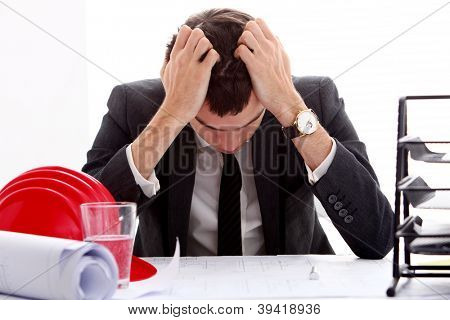Businessman in stress holding his head with hands sitting at the table