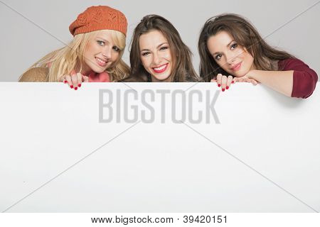 Three smiling girls with advert board