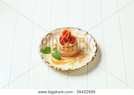 small cake with vanilla cream and raspberries sprinkled with orange peel, on the plate