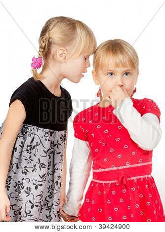 Portrait of little girl wearing black telling a secret to her friend over a white background