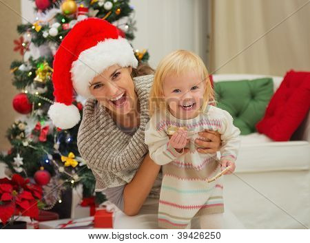 Portrait Of Laughing Mother And Eat Smeared Baby Near Christmas
