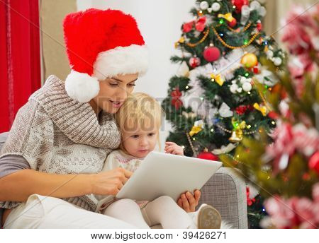 Mother And Baby Girl Using Tablet Pc Near Christmas Tree