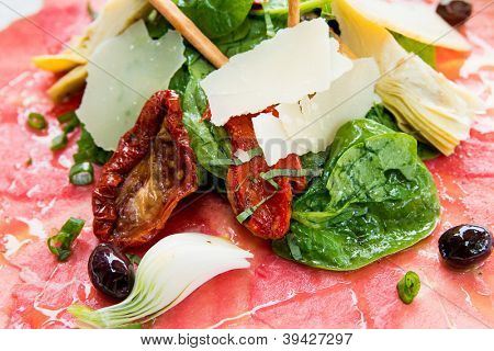 Fresh Sliced raw beef meat with leaf lettuce on table