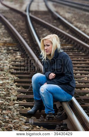 a young woman is sad, anxious and depressed. sitting on a track and is lonely