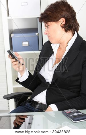 Businesswoman Pulling A Face At A Text Message