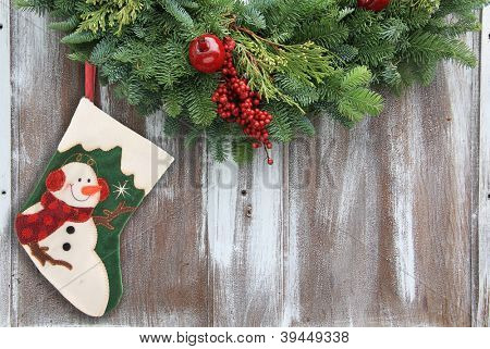 Christmas garland with a snowman stocking on a rustic wooden background.