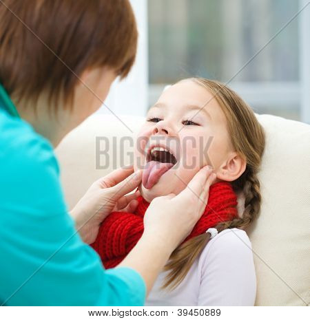 Doctor is examining a little girl who showing tongue, indoor shoot