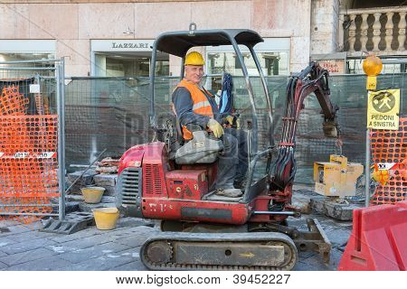Worker sitting in cab of lift truck for paving